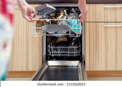 Image of girl's hand opening dishwasher with dirty dishes