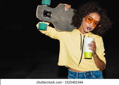 Image of glamour african american girl in streetwear drinking soda and holding skateboard at night outdoors