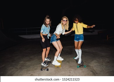 Image of glamour multinational girls in streetwear smiling and riding skateboards at night outdoors