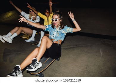 Image of glamour multinational girls in streetwear smiling and riding on skateboards at night party outdoors