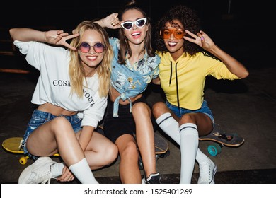 Image of glamour multinational girls in streetwear smiling and sitting on skateboards at night party outdoors