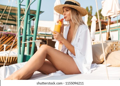 Image of glamour pretty woman 20s in straw hat drinking orange juice while sunbathing and sitting on luxury bed on beach during summer sunny day