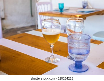 Image of glasses with cold beer and water on the table