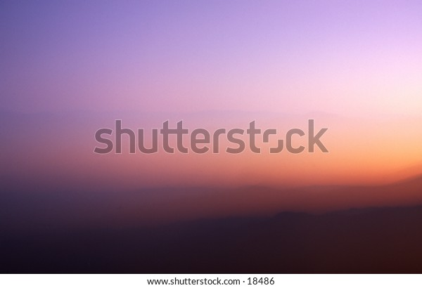 The image is of a glowing mountain sunset displaying a multitude of muted pastel colors.