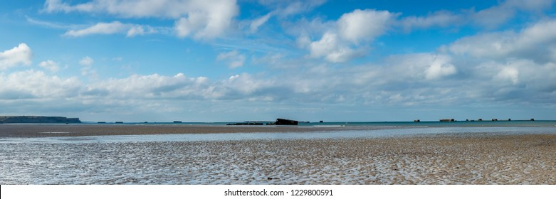 image of gold beach in normandy near arromanches in france showing the golden sand, waters of the channel and stormy skies with the remains of the World War II harbour built by the British on D Day
