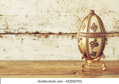image of gold faberge egg on wooden table. vintage filtered