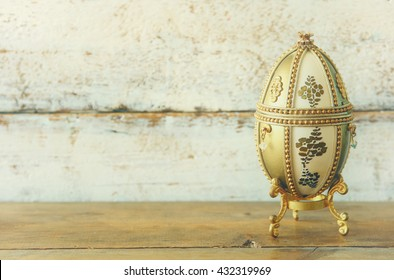 image of gold faberge egg on wooden table. vintage filtered and toned