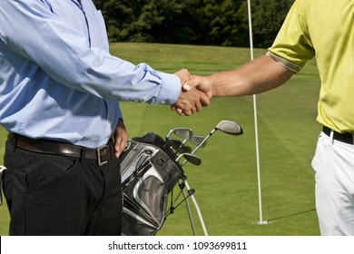 Image of Golfer and caddy shaking hands