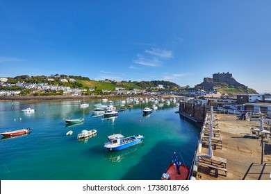 Image of Gorey Harbour with fishing and pleasure boats, the pier bullworks and Gorey Castle in the background with blue sky. Jersey, Channel Islands, UK