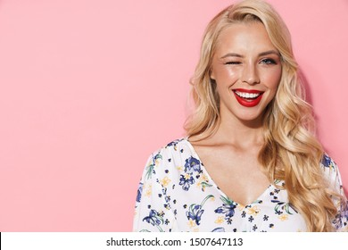 Image of gorgeous woman with long blond hair smiling and winking at camera isolated over pink background