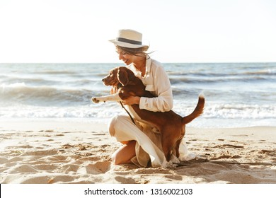 Image of gorgeous woman in straw hat hugging her brown dog while walking by seaside