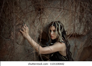 Image of Gorgon Medusa, braid hair and gold snakes, close-up portrait. Gothic make-up in green shades. Background of wild stones. Long black claws and a predatory look.