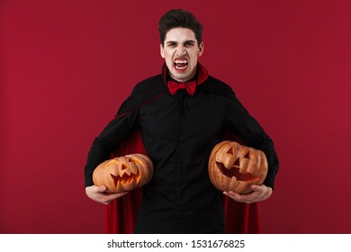Image of gothic vampire man with fangs in black halloween costume holding carved pumpkins isolated over red wall
