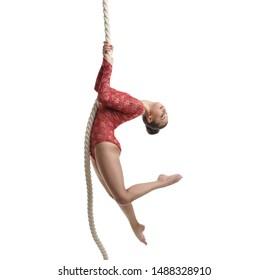 Image of graceful female gymnast hanging on rope