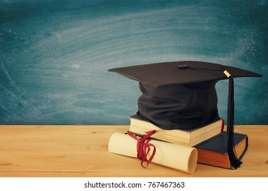 Image of graduation black hat over old books next to graduation on wooden desk. Education and back to school concept
