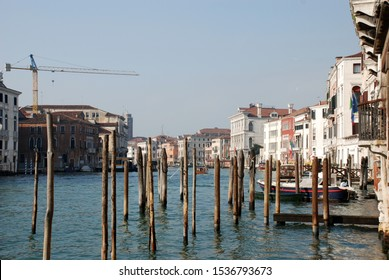 Image of the Grand Canal of Venice typical buildings Italy, wooden doors and windows with arcades balconies with baluster and with iron railings mooring of boats on a sunny winter day general image