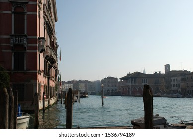 Image of the Grand Canal of Venice typical buildings Italy, wooden doors and windows with arcades balconies with baluster mooring of boats on a sunny winter day general image