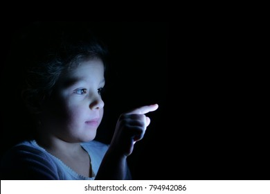 image for graphic implementation - A little girl with her finger presses in front of her and bright futuristic graphics appear. Concept of: future, network, technology, security for children.