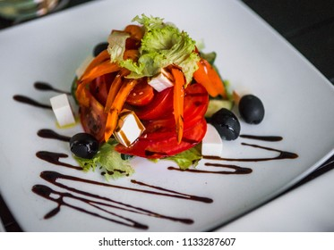 Image of greek salad beautifully decorated on a square white plate, selective focus