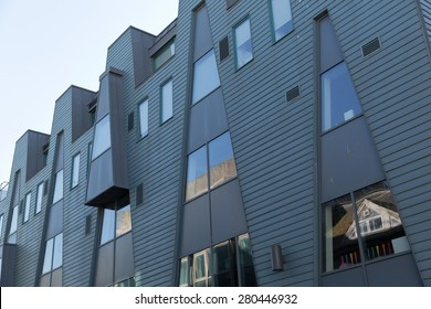 An image of a grey metal cladded facade with angled lines dividing the material of the facade