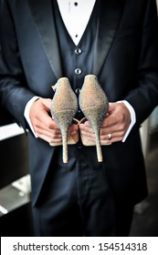An image of a groom holding bride's shoes