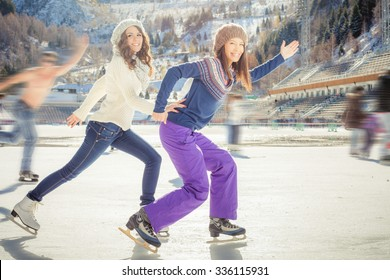 Image of group funny teenagers ice skating outdoor at ice rink, holding hands at Medeo stadium. Winter activities for a good mood and healthy mind. Action and speed