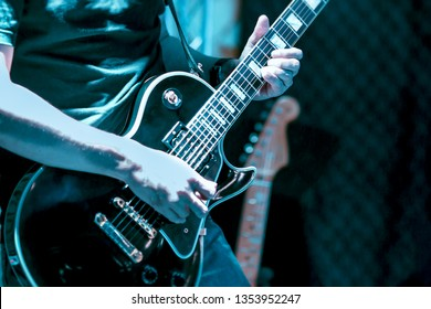ฺBlurred image of Guitarist on stage for background, soft and blur concept. Close up hand playing guitar. young musician playing guitar, live music background.Band performs on stage, rock  concert.