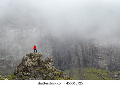 Image of a guy watching misty mountains. Trending concept of a small people and powerful nature