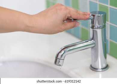 Image of hand closing valve on sink in bathroom. Water dripping to stop running as hand turn off the faucet. Save the water concept.Detect-a-Leak week.