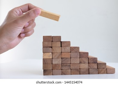 Image of hand holding blocks wood game to growing up of business. Risk of management and strategy plan.