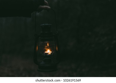 image of a hand holding a lit lantern in the dark of the woods
