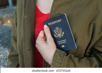 Image of a womanâ??s hand holding a passport