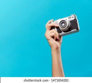 Image of hand with phone on empty blue background