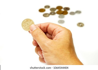 Image of hand picking up 500 Japan Yen currency coins from stack isolate on white background. Make with paths.