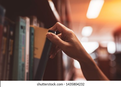 Image of a hand selecting a book from a bookshelf