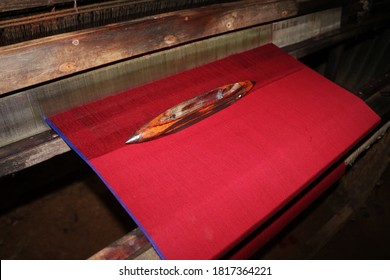 Image of a handloom shuttle on a red colored fabric.