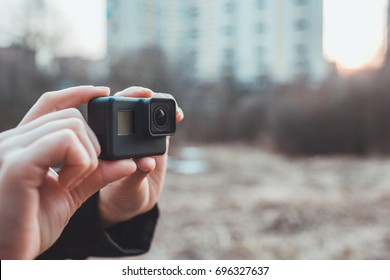 an image of hands holding small action camera