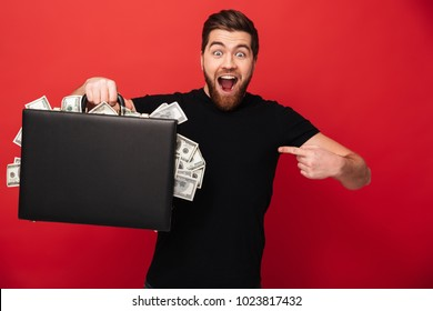 Image of handsome bearded man standing isolated over red background wall holding suitcase full of money pointing. Looking camera.