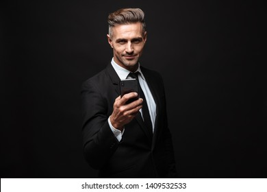 Image of a handsome business man posing isolated over black wall background using mobile phone.