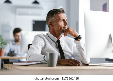 Image of handsome businessman 30s wearing white shirt and tie sitting at desk in office by computer and looking aside