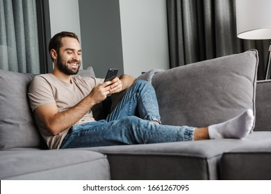 Image of a handsome cheerful happy young positive man indoors at home on sofa using mobile phone.