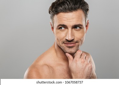 Image of handsome cheerful mature man standing isolated over grey wall background naked. Looking aside.