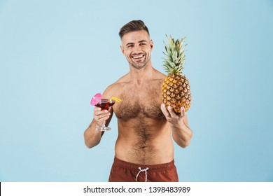 Image of a handsome excited happy adult man posing isolated over blue wall background drinking cocktail holding pineapple.