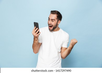 Image of a handsome excited young man using mobile phone isolated over blue wall background make winner gesture.
