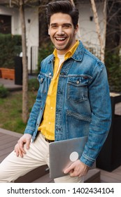 Image of a handsome happy cheerful young business man near cafe outdoors holding laptop computer.
