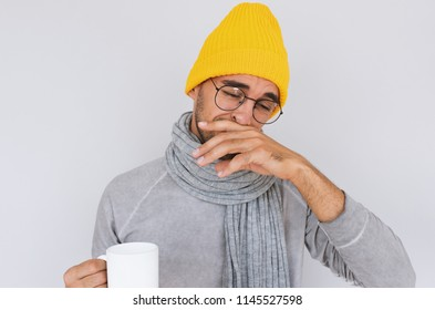 Image of handsome male caught cold when had walk outdoors in winter or autumn. Portrait of sick man have grippe wearing glasses, yellow hat, grey sweater and scarf. People, health, medicine concept