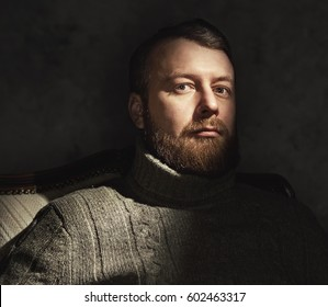 An image of a handsome man with a beard. Studio shot