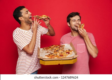 Image of a handsome pleased happy young men friends isolated over red wall background holding big pizza eating.