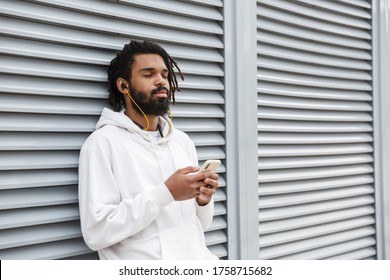 Image of a handsome relaxing young man walking outdoors with earphones using mobile phone
