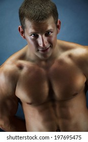 Image of handsome shirtless man looking at camera over dark background